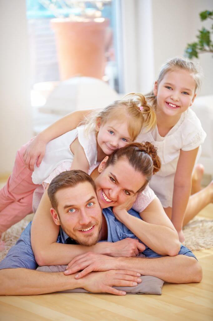 Glückliche Familie und zwei lachende Kinder im Wohnzimmer