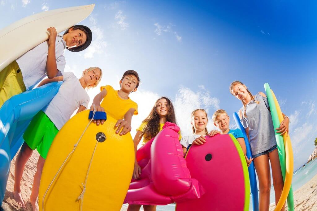 Low angle shot group of kids standing with body boards, surfboards, inflatable rings and matrasses, swimming sticks on sandy sunny beach ready to swim